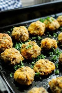 low carb sausage keto balls on a black baking tray with parsley garnished over it
