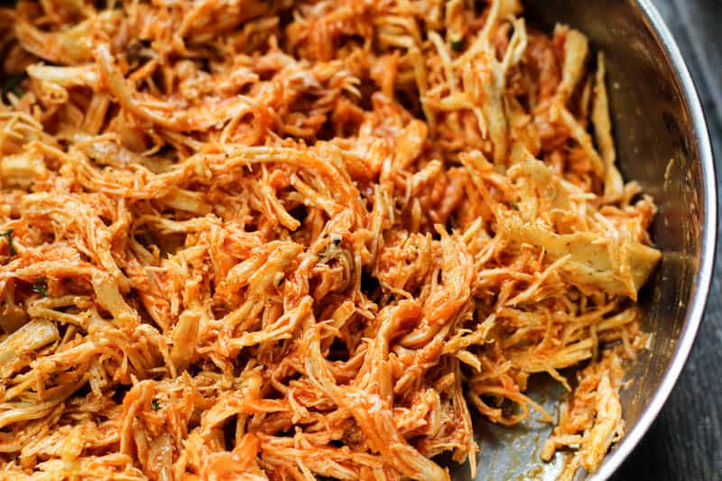 shredded chicken covered in buffalo sauce in a pan