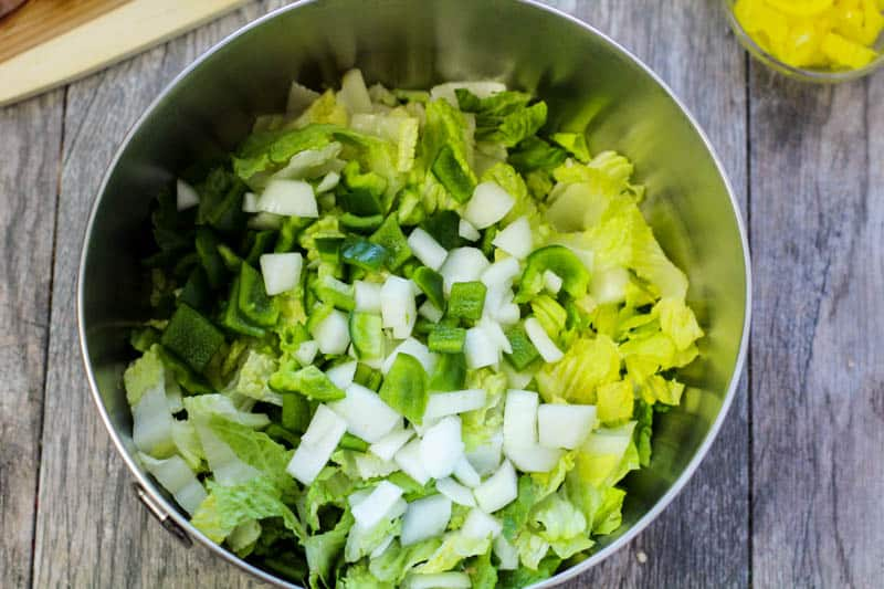 chopped lettuce, onions, and green bell pepper in a metal mixing bowl