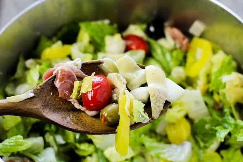 antipasto salad on a wooden spoon