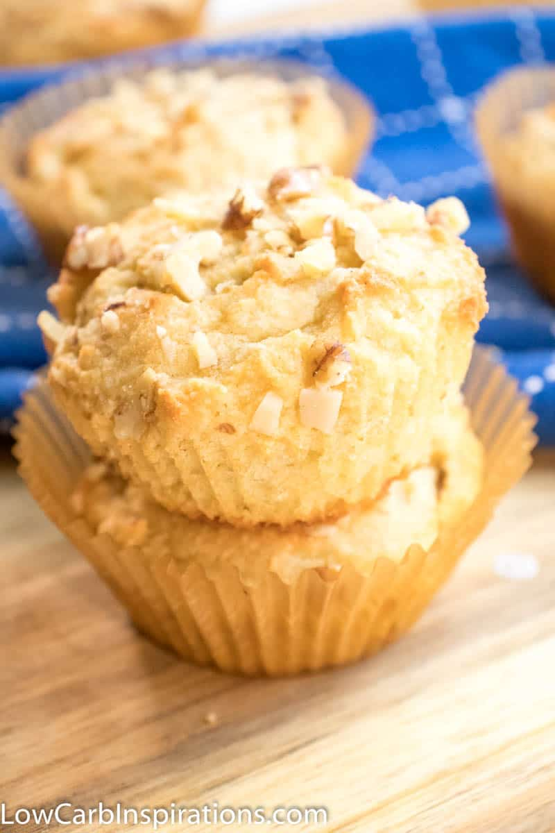 Banana Nut Keto Breakfast Muffins laying on a wooden cutting board with blue cloth in the background