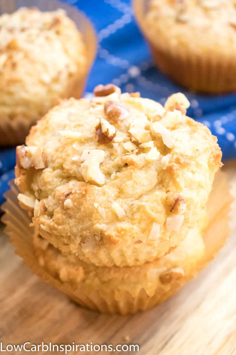 Up close picture of banana nut keto breakfast muffins stacked on a wooden cutting board with blue cloth in the background