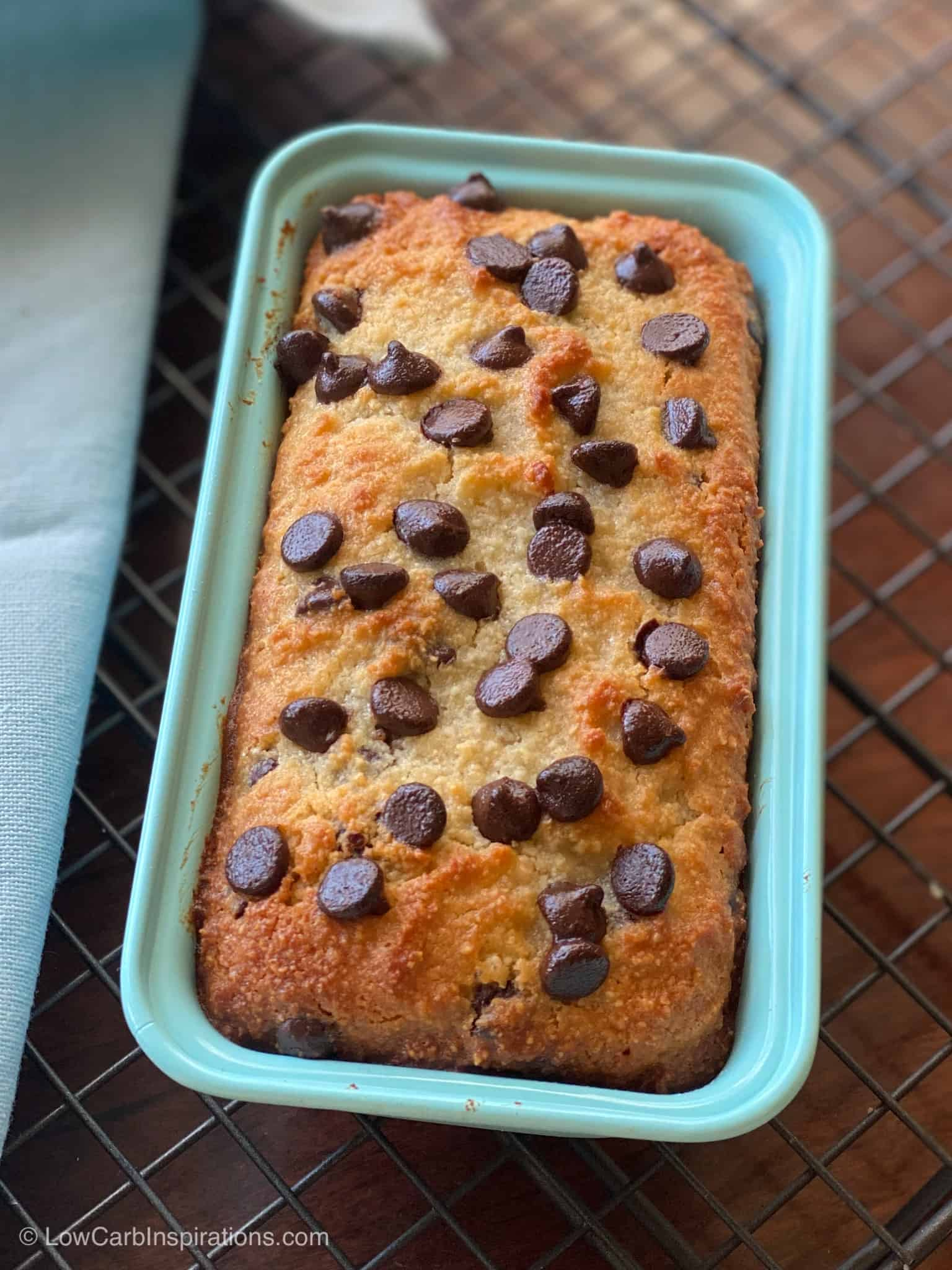 Baked Keto Chocolate Chip Banana Bread in a blue mini bread pan on a wire rack