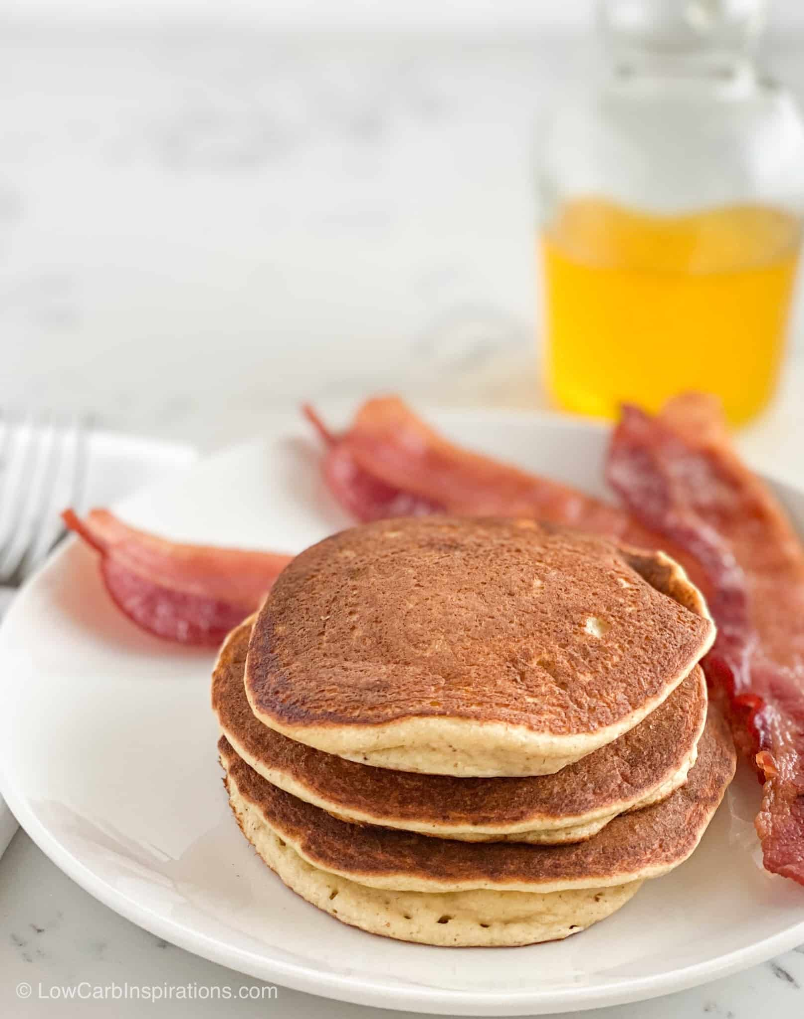 3 Fluffy Keto Pancakes served with bacon and a side of banana syrup that's sugar free