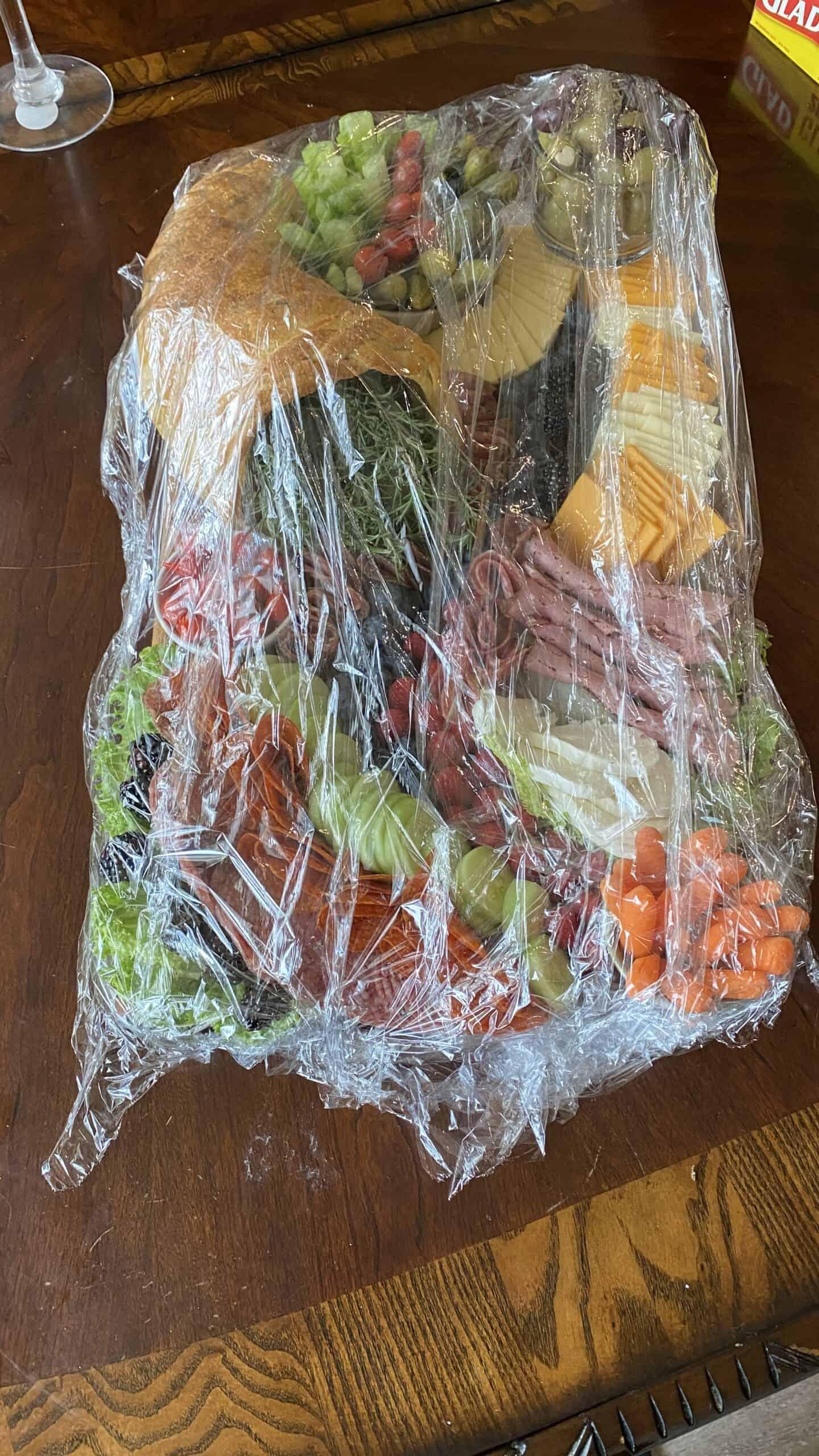 Easy Keto Charcuterie Board with keto cornucopia bread wrapped in saran wrap