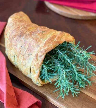 Keto Cornucopia Bread Recipe stuffed with rosemary and set on a cutting board to display