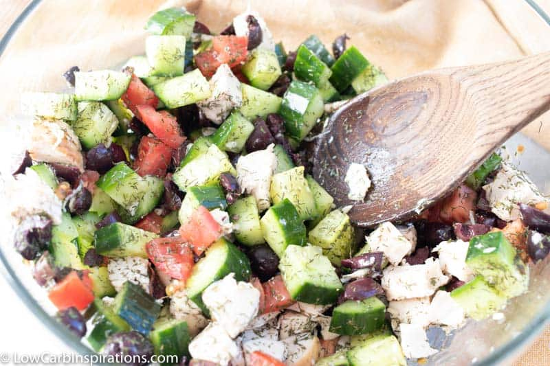 mixing greek chicken salad ingredients in a clear bowl with a wooden spoon