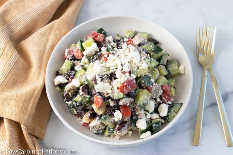 overhead photo of greek salad with chicken in a white bowl not mixed together with forks on a table
