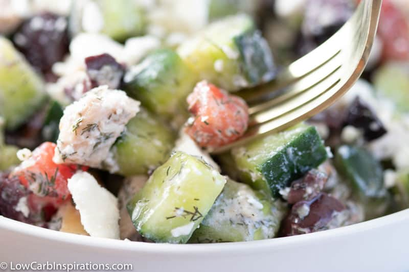close up of greek salad with chicken in a white bowl with a gold fork