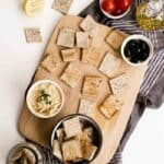 Homemade Almond Flour Crackers on a wood cutting board with dip in a bowl