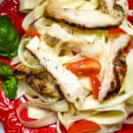 Close up photo of keto pasta noodles with butter sauce, chicken, and tomatoes with a side of basil as a garnish served on a red plate