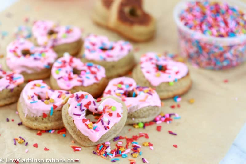 heart shaped keto glazed donuts with sprinkles on a table