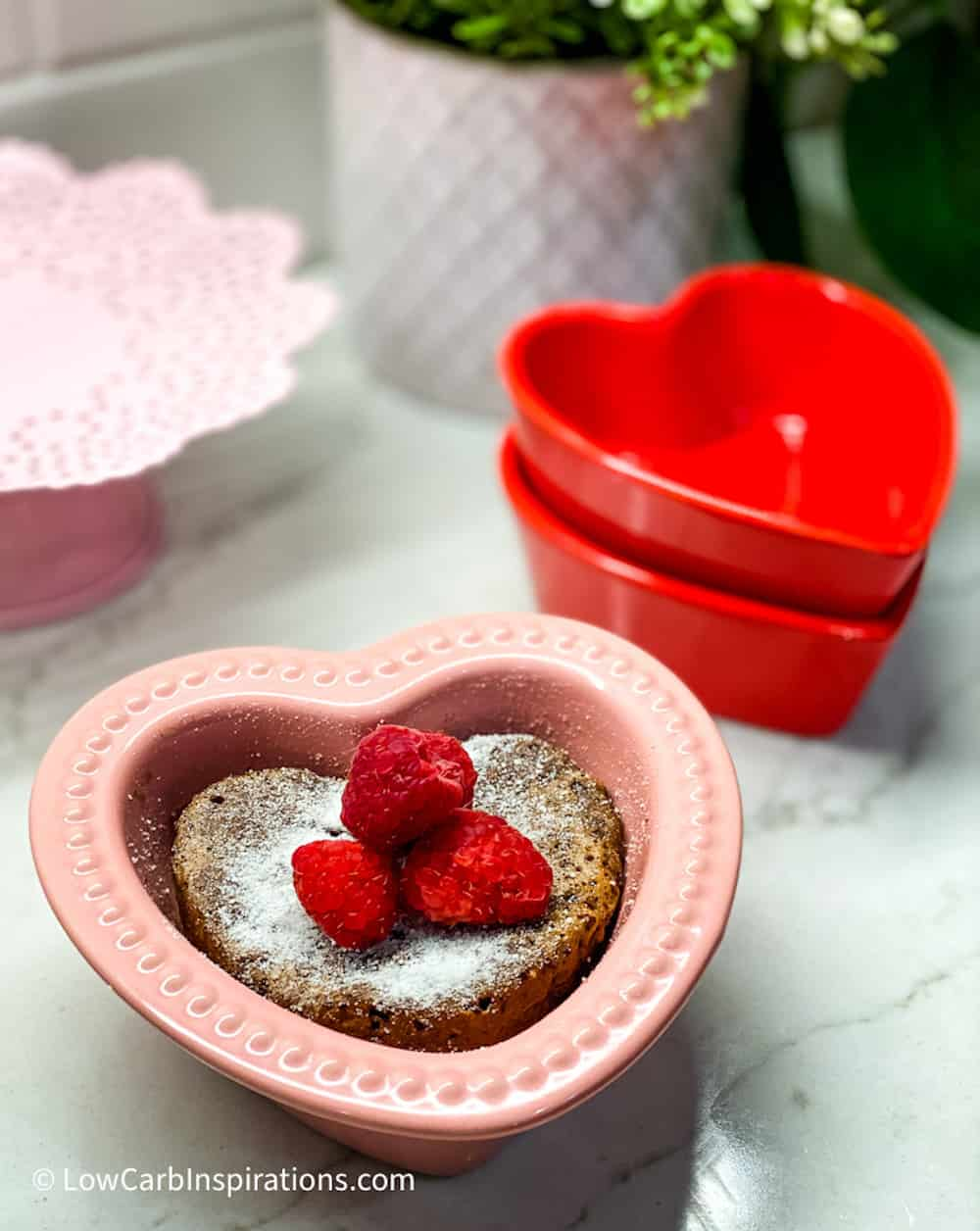 Heart shaped chocolate cake dusted with sweetener and topped with Raspberries served in a pink cake pan.