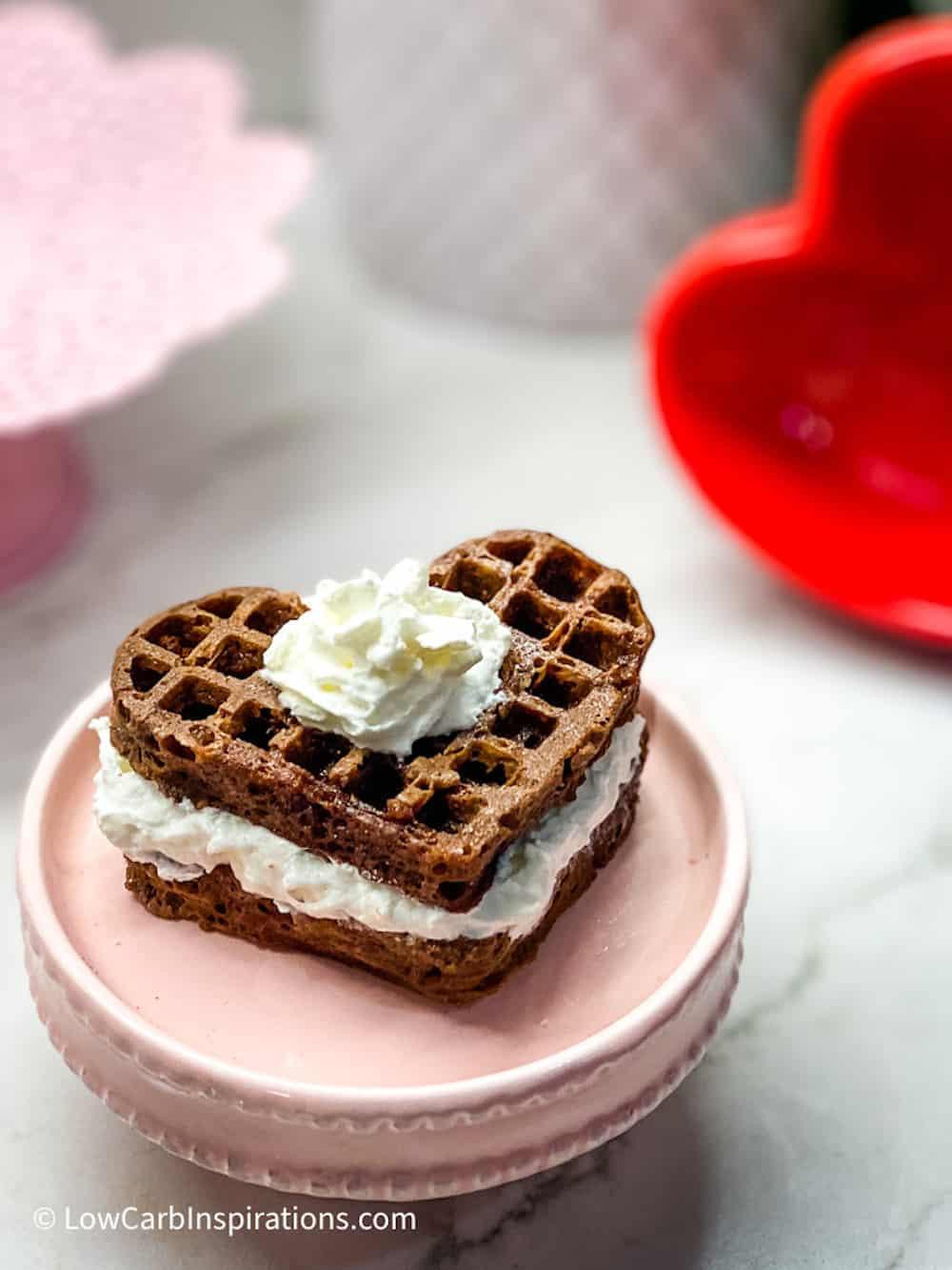 Heart shaped chocolate waffle cake on a pink cake plate stand