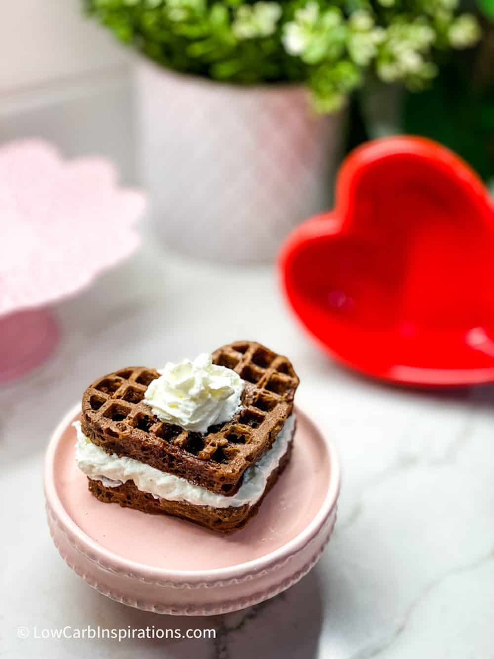 Chocolate Heart Shaped Waffle Cake on a pink cake plate topped with whipped cream