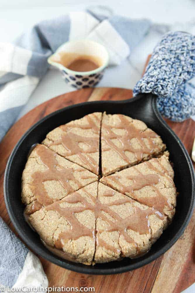 delicious cinnamon scones in a cast iron skillet with cinnamon drizzled on top