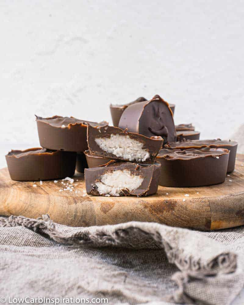 chocolate coconut bonbons stacked on a wood cutting board