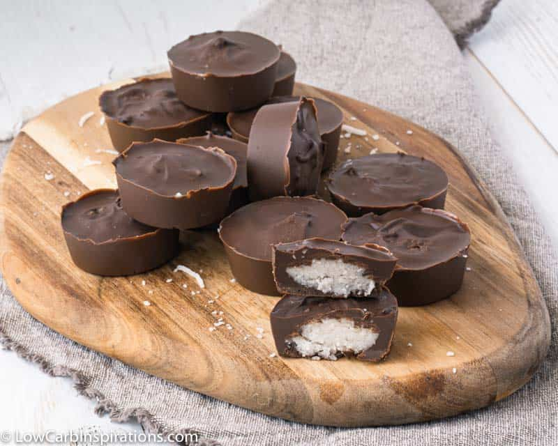 far away photo of chocolate coconut bonbons stacked on a wood cutting board