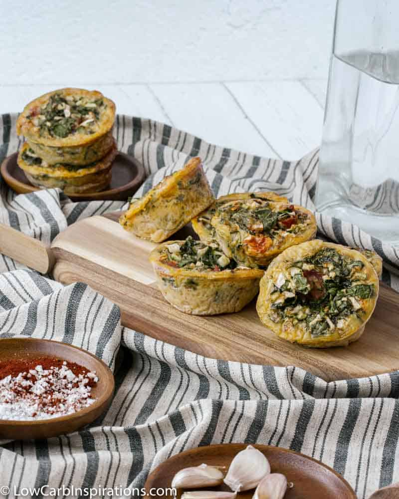 stacked egg muffins on a wood cutting board with a small bowl on the side