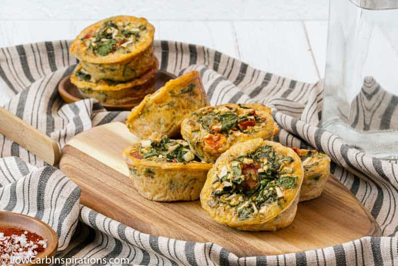 far away photo of stacked egg muffins on a wood cutting board