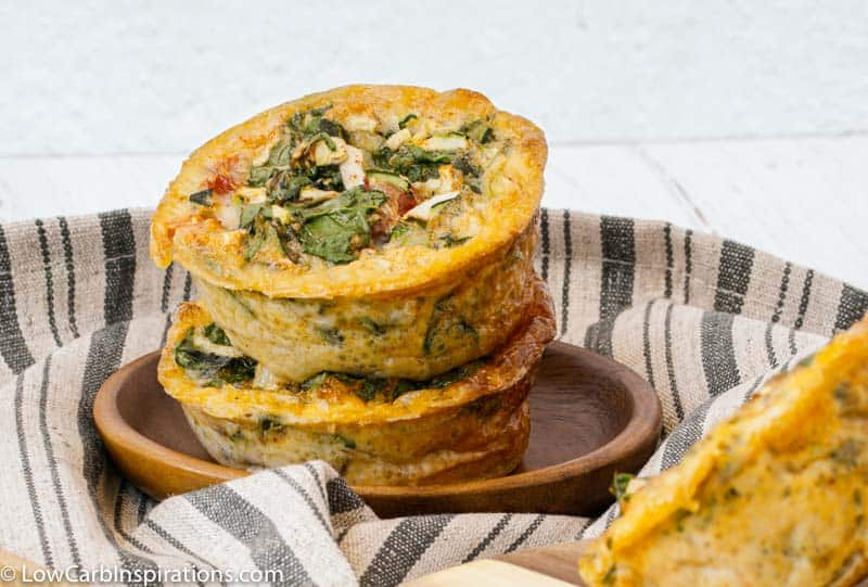 close up of stacked Keto Zucchini Egg Muffins Recipe on a brown plate with a towel under
