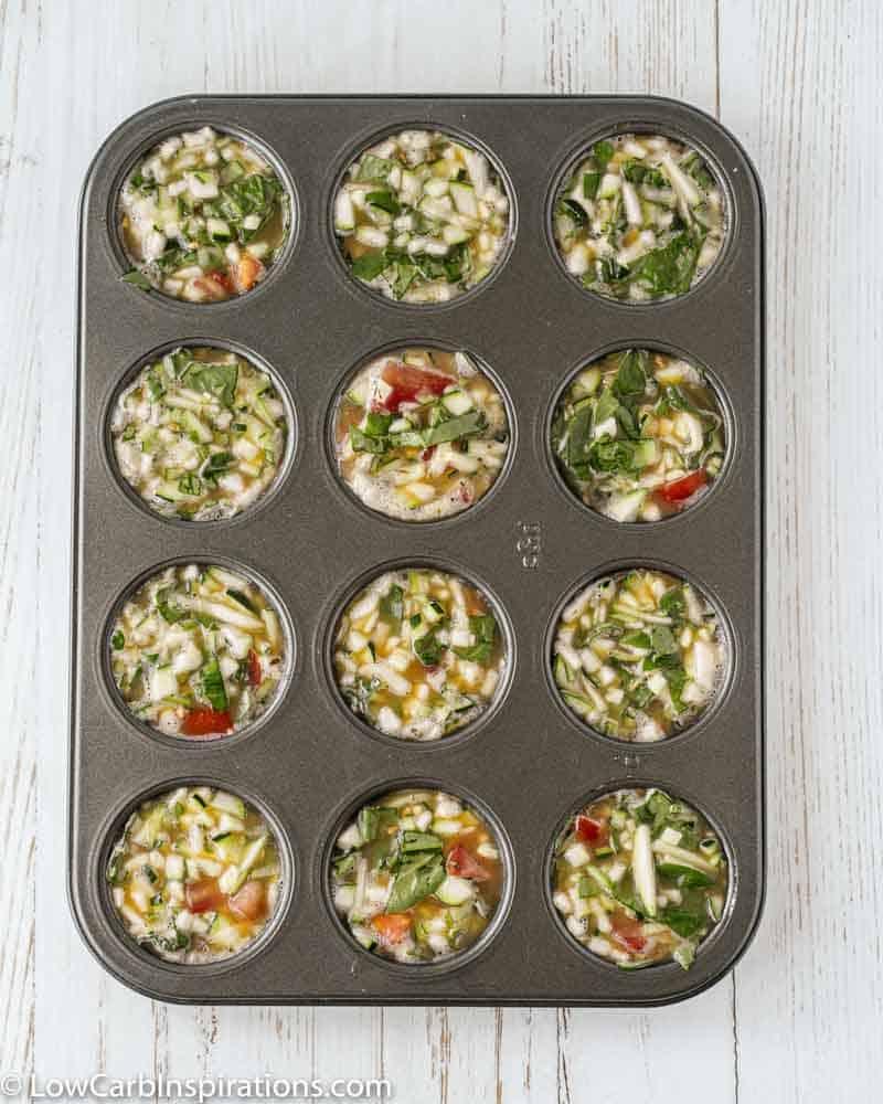 zucchini egg muffin recipe in a muffin pan ready to bake