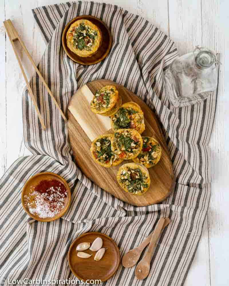 far away overhead photo of stacked zucchini egg muffins on a wood cutting board