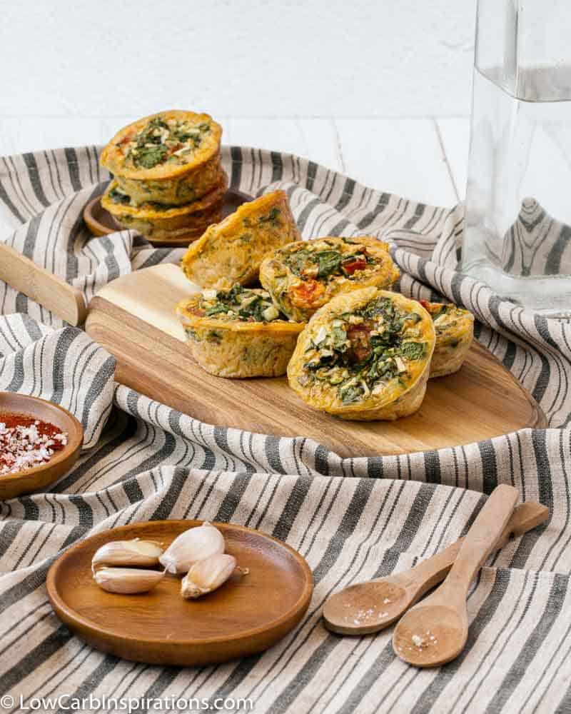 stacked zucchini egg muffins on a wood cutting board