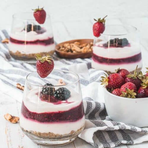 yogurt parfait recipe on a table with strawberries next to it and more parfaits in the background
