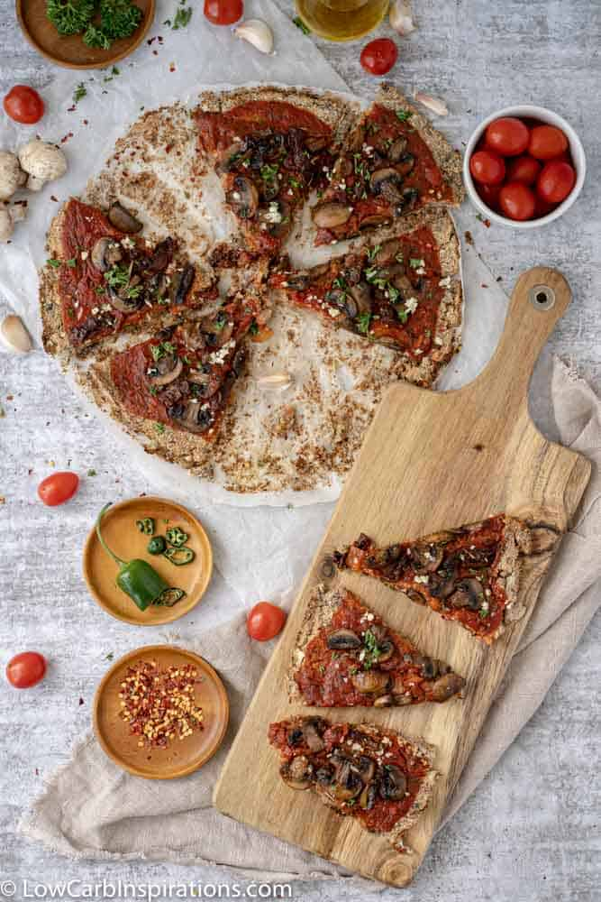 overhead view of Mushroom Pizza Recipe with Cauliflower Crust sliced on a wood serving board and parchment paper
