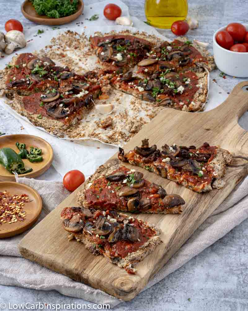 close up of Mushroom Pizza Recipe with Cauliflower Crust on a wood serving board with sliced pizza in the background