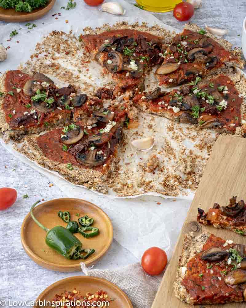 Mushroom Pizza Recipe with Cauliflower Crust cut into slices on parchment paper