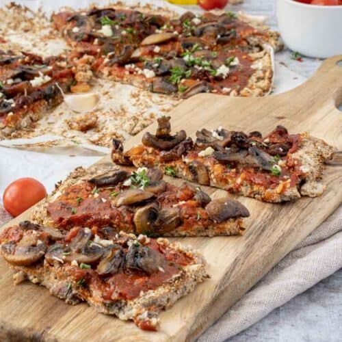 close up of Mushroom Pizza Recipe with Cauliflower Crust on a wood serving board