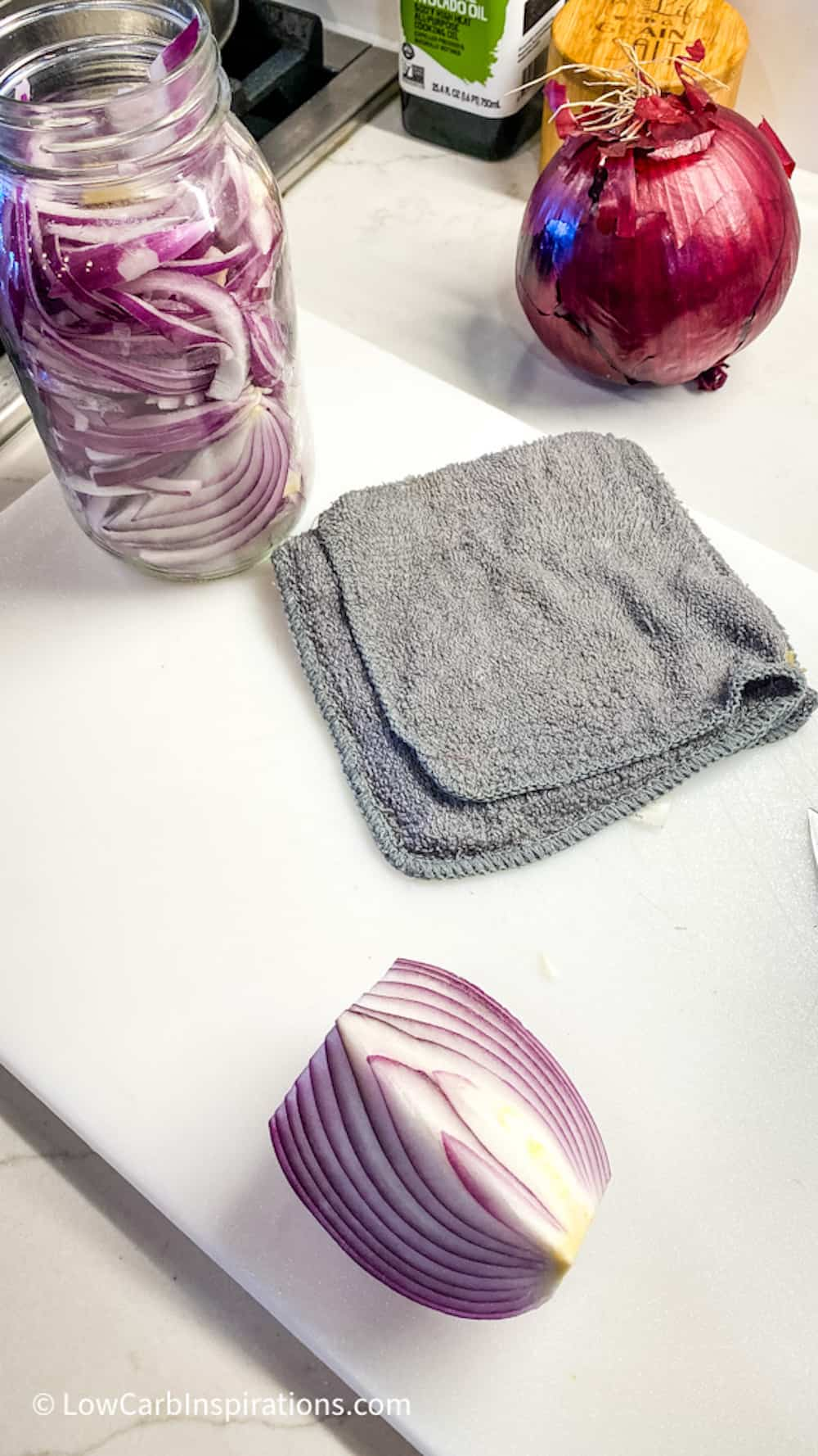 Dish towel next to cut red onions