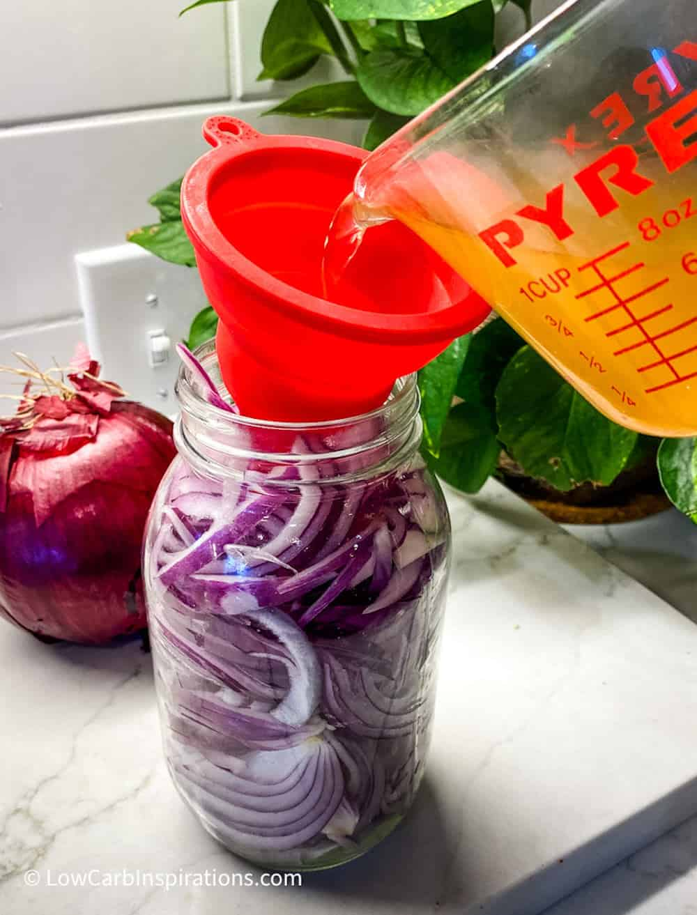 Pouring pickling juice into a mason jar filled with red onions