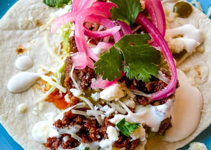 Taco topped with red onions on a blue plate