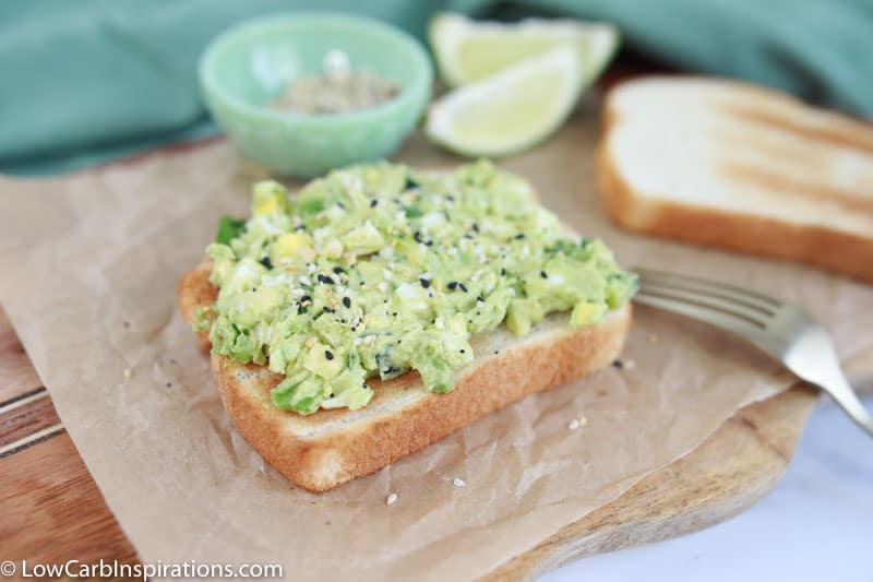 close up of keto bread topped with avocado egg salad on a wood cutting board with lies and seasonings in the background