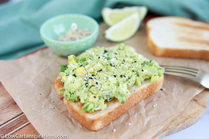 low carb bread topped with avocado egg salad on a wood cutting board with lies and seasonings in the background