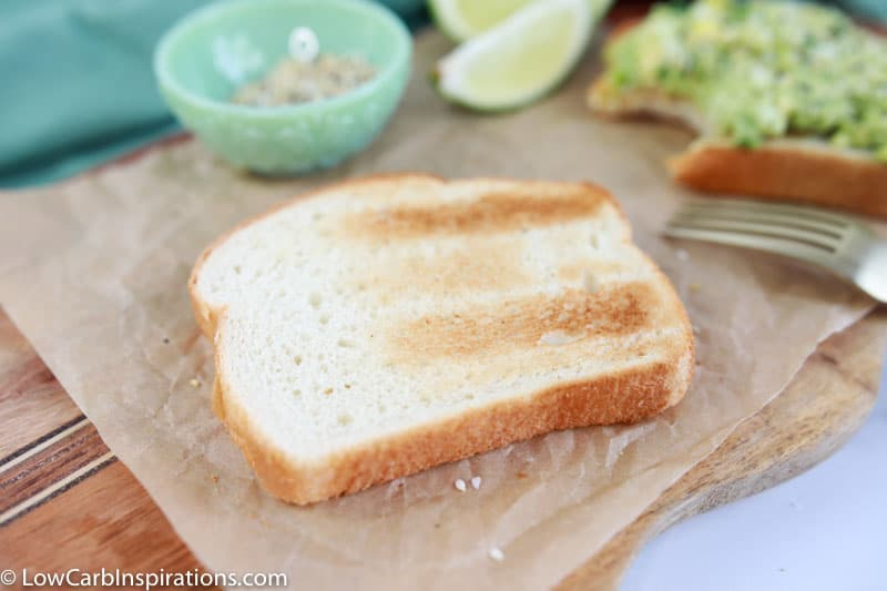 low carb bread on a wood cutting board with lies and seasonings in the background