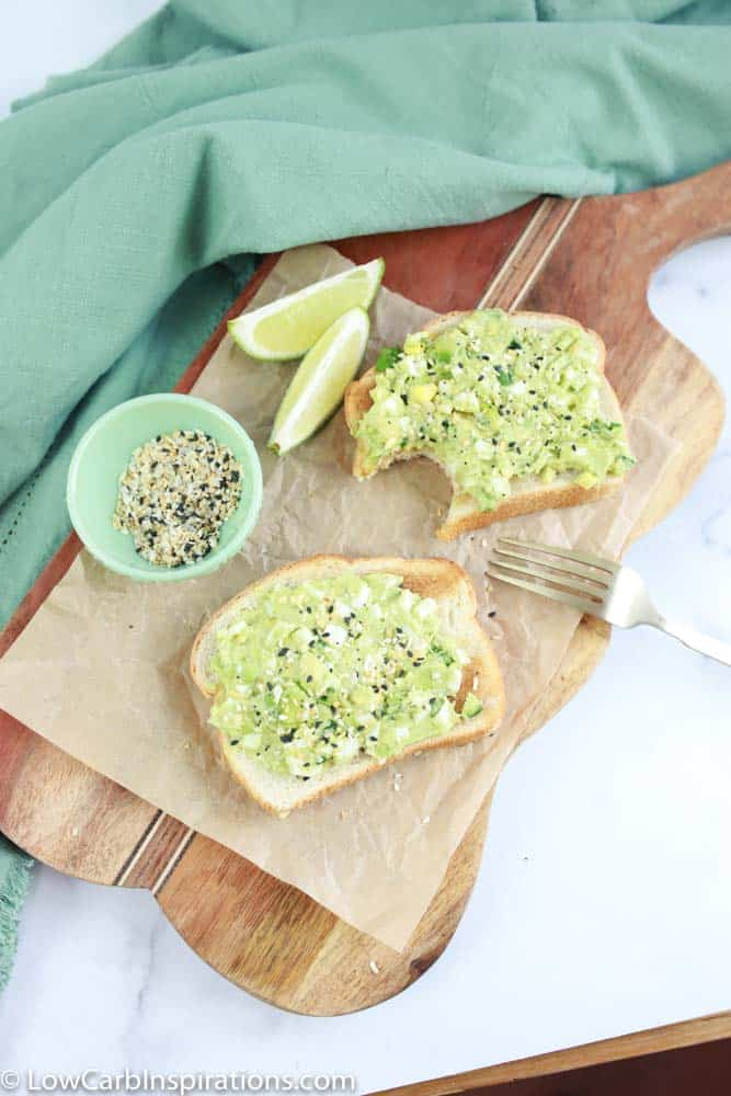 overhead photo of avocado egg sandwich on brown parchment paper with lemons and seasoning on the side