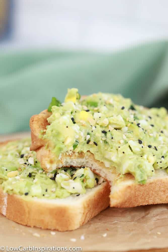 close up of avocado egg salad toast on brown parchment paper with a bite taken