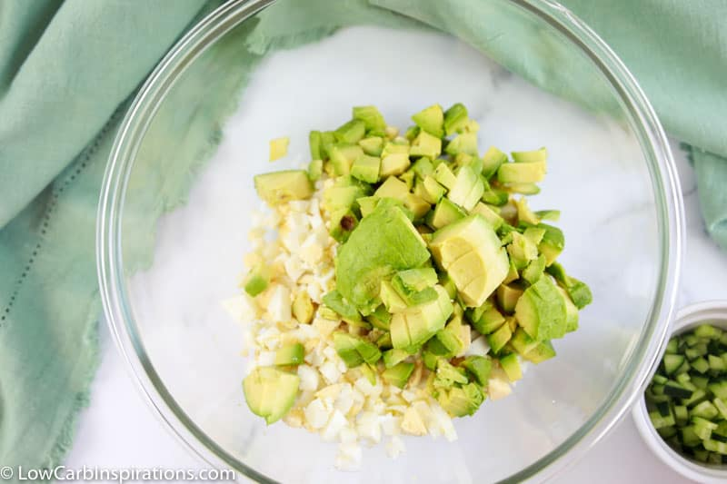 diced eggs and avocado in a clear mixing bowl on a table