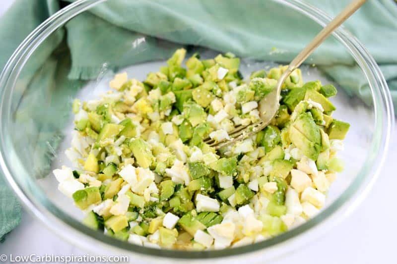 all the avocado egg salad toast ingredients in a clear bowl ready to be mixed together with a fork in the bowl