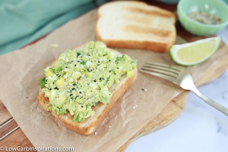 avocado egg salad recipe made on brown parchment paper with a fork, lime and seasonings on the side