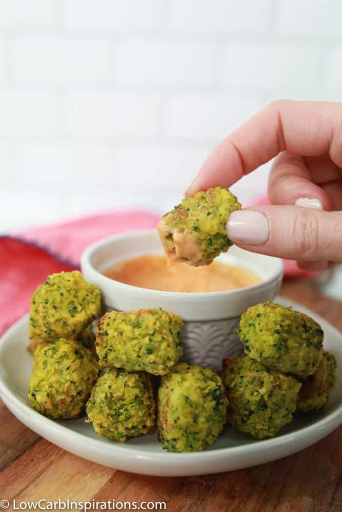 keto broccoli bites on a white plate with a white bowl of sriracha dipping sauce