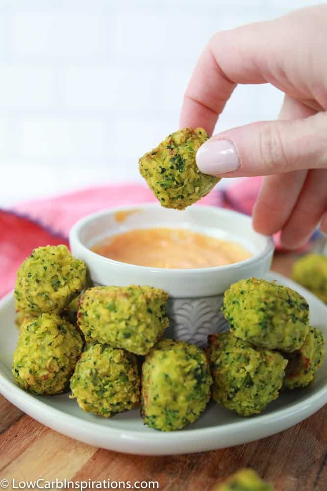 baked broccoli bites a white plate with a white bowl of dipping sauce and a handing holding one close up