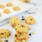 sweet and salty cookies stacked on a table with more cookies in the background on a cookie sheet
