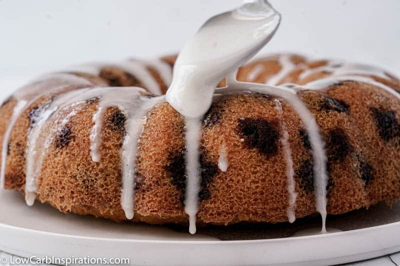 drizzling the sugar free glaze over the lemon blueberry pound cake with a spoon