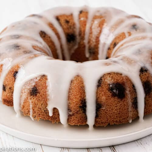 close up of finished lemon blueberry pound cake on a white plate on a table