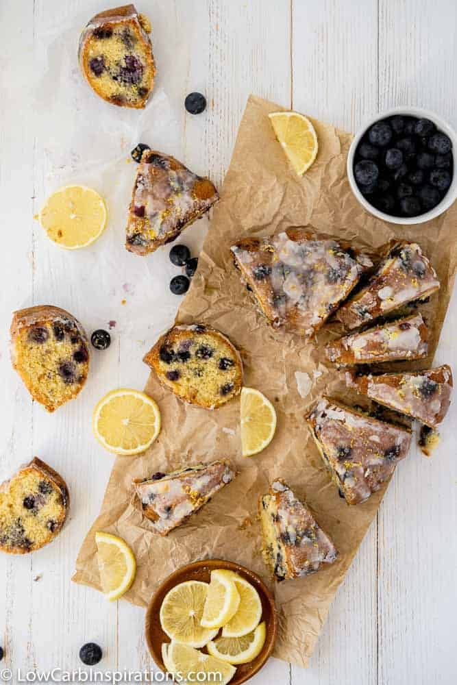 overhead photo fo cut pound cake on brown parchment paper with lemon slices and blueberries on a table